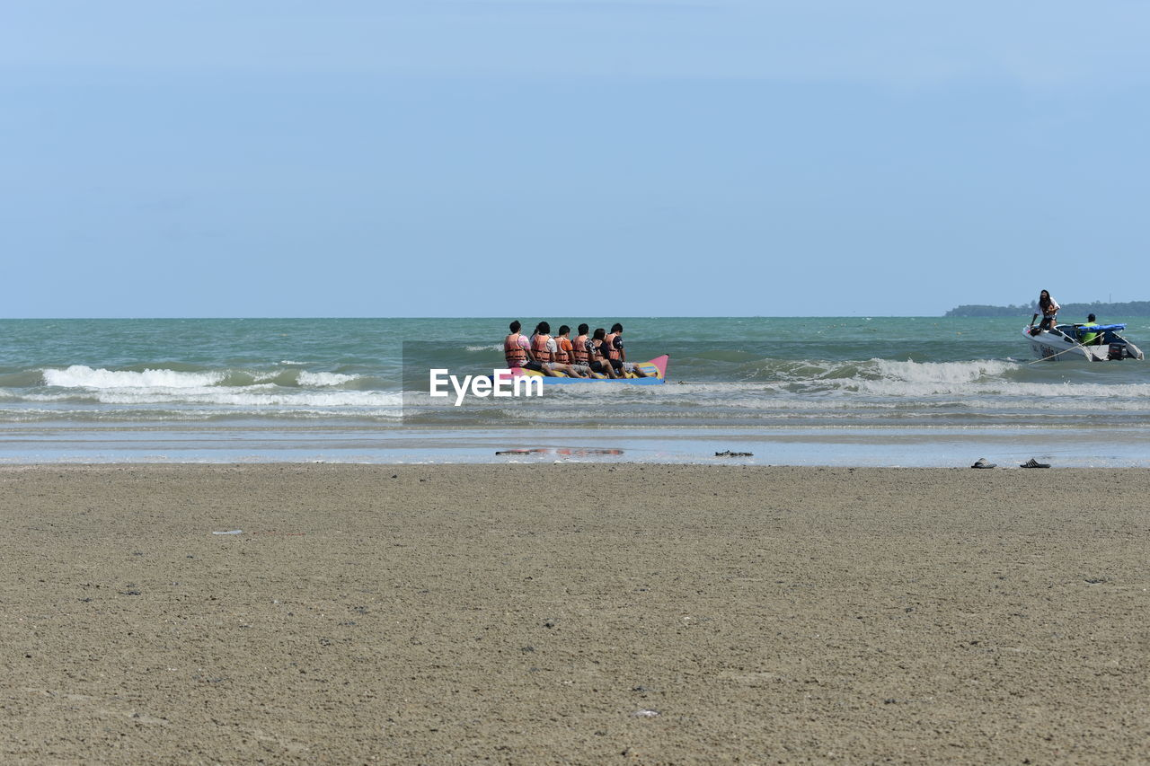 sea, water, beach, land, sky, horizon over water, group of people, horizon, real people, motion, lifestyles, beauty in nature, leisure activity, day, nature, sport, transportation, men, sand, outdoors
