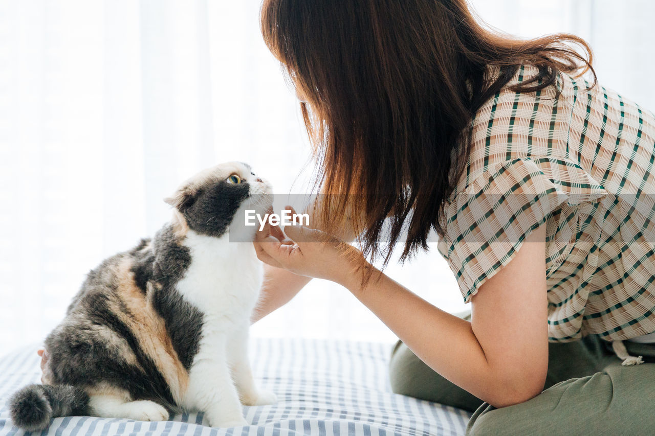 Side View Of Woman Playing With Cat On Bed At Home