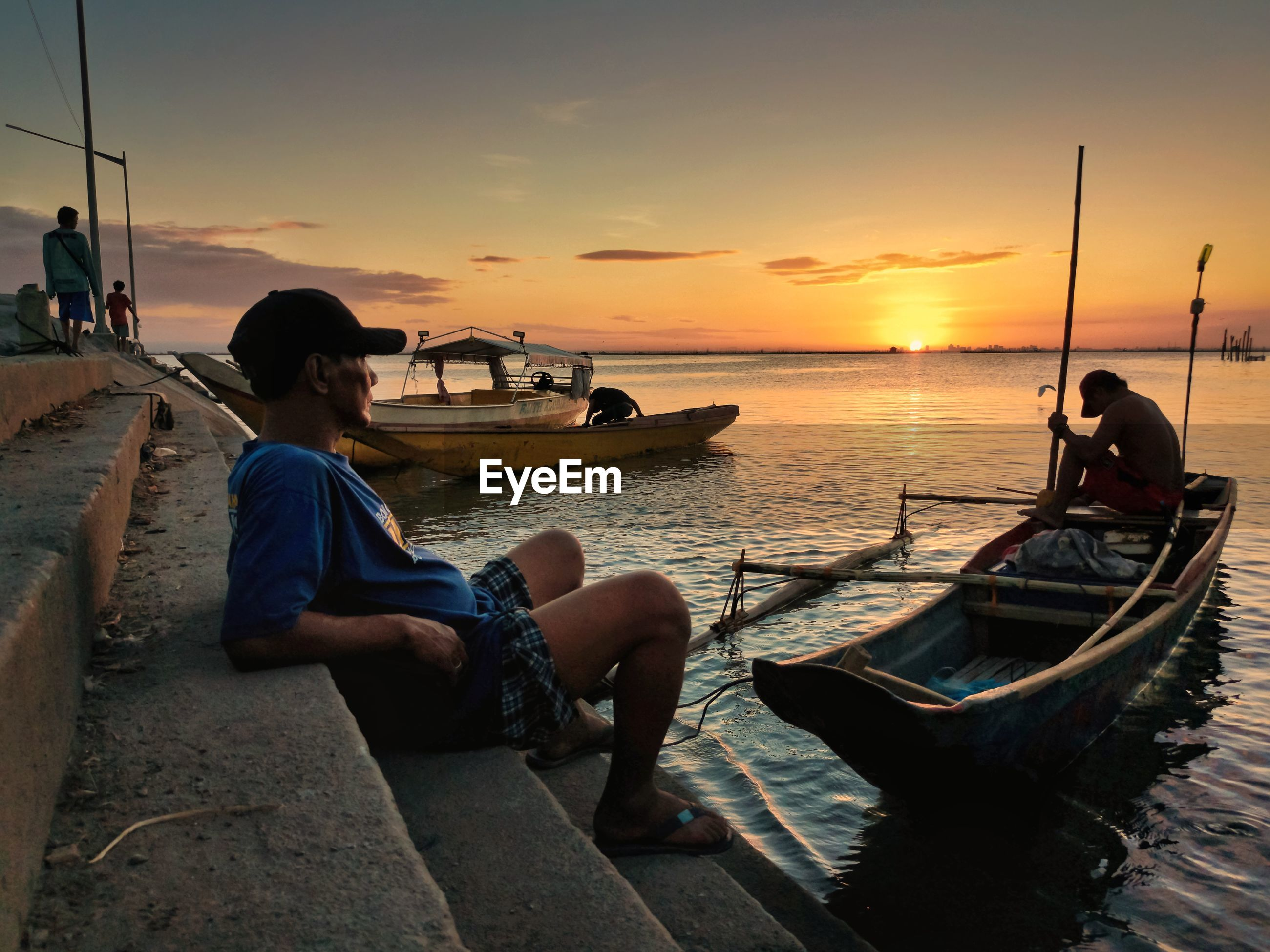 PEOPLE SITTING ON BOAT AGAINST SEA DURING SUNSET