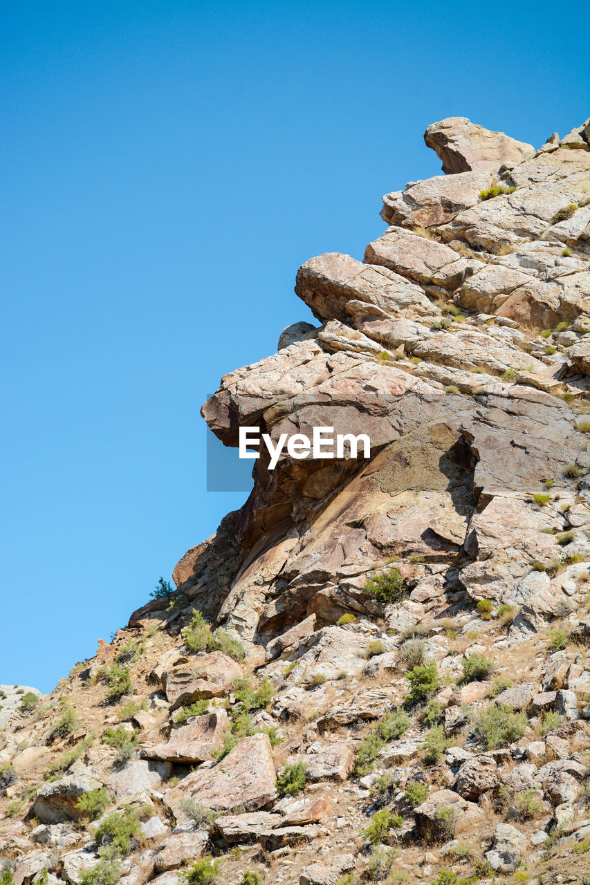 rock - object, rock formation, clear sky, low angle view, geology, cliff, nature, rock, blue, mountain, adventure, outdoors, no people, day, physical geography, beauty in nature, rock hoodoo, sky, high