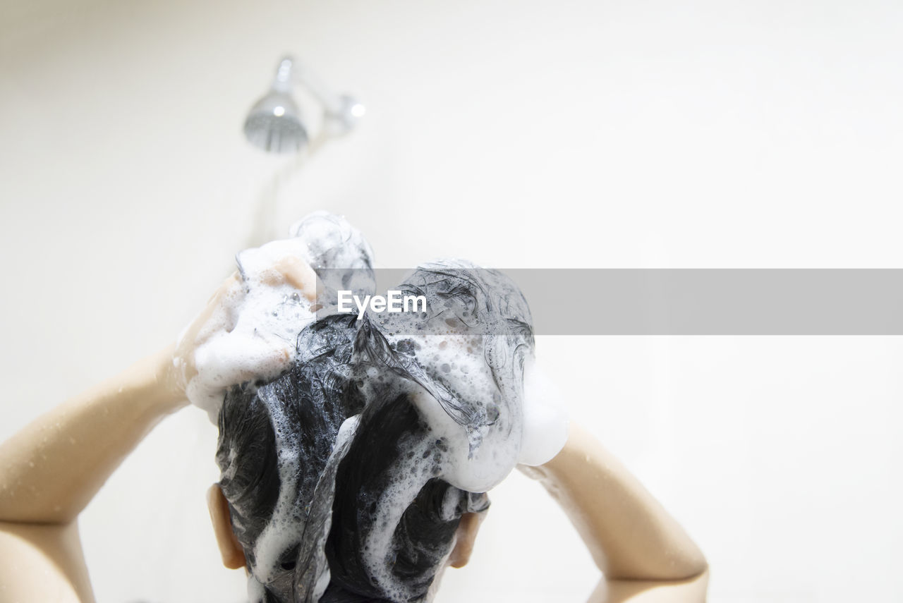 Rear view of woman washing hair in bathroom