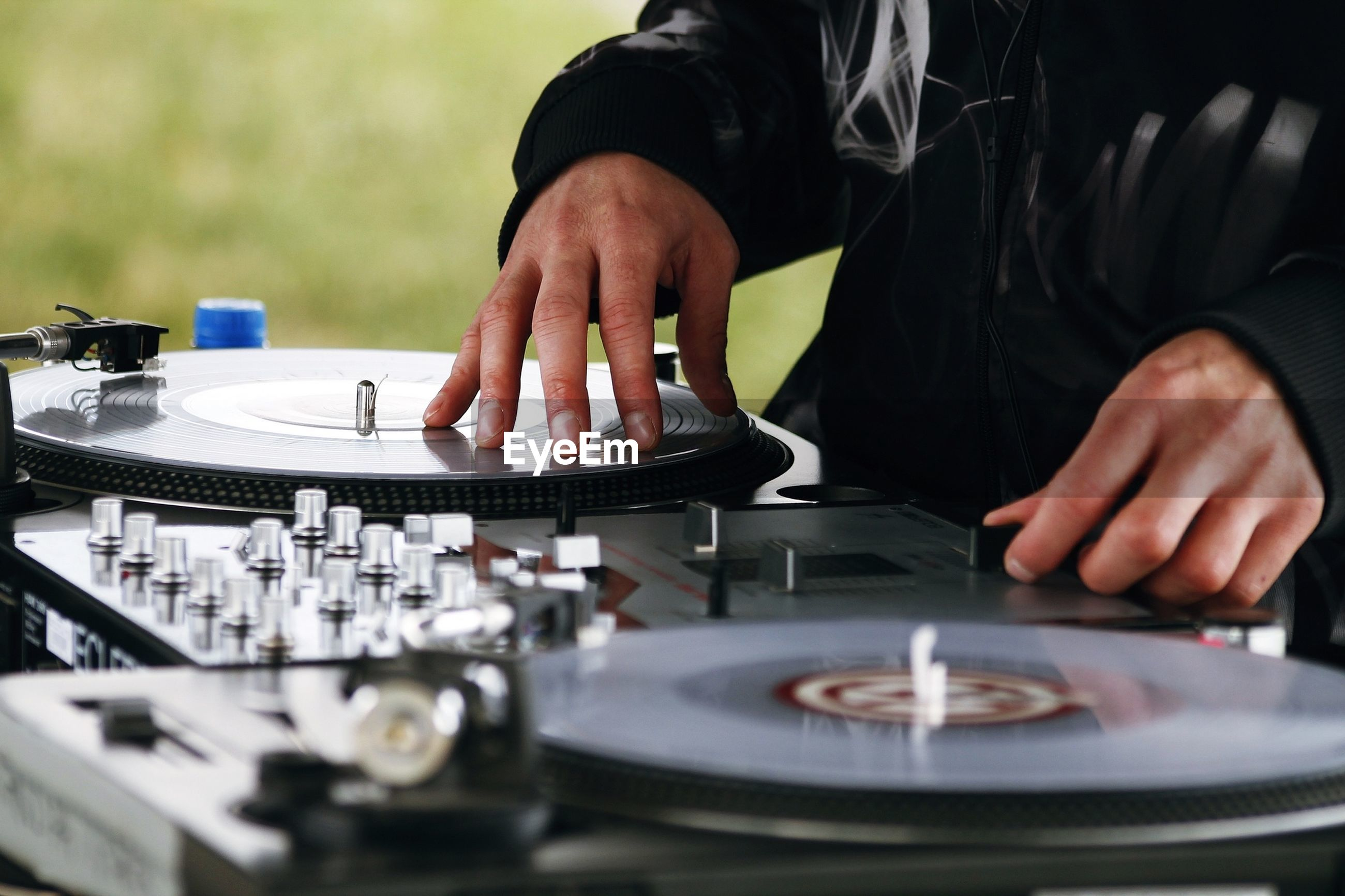 Midsection of man playing records