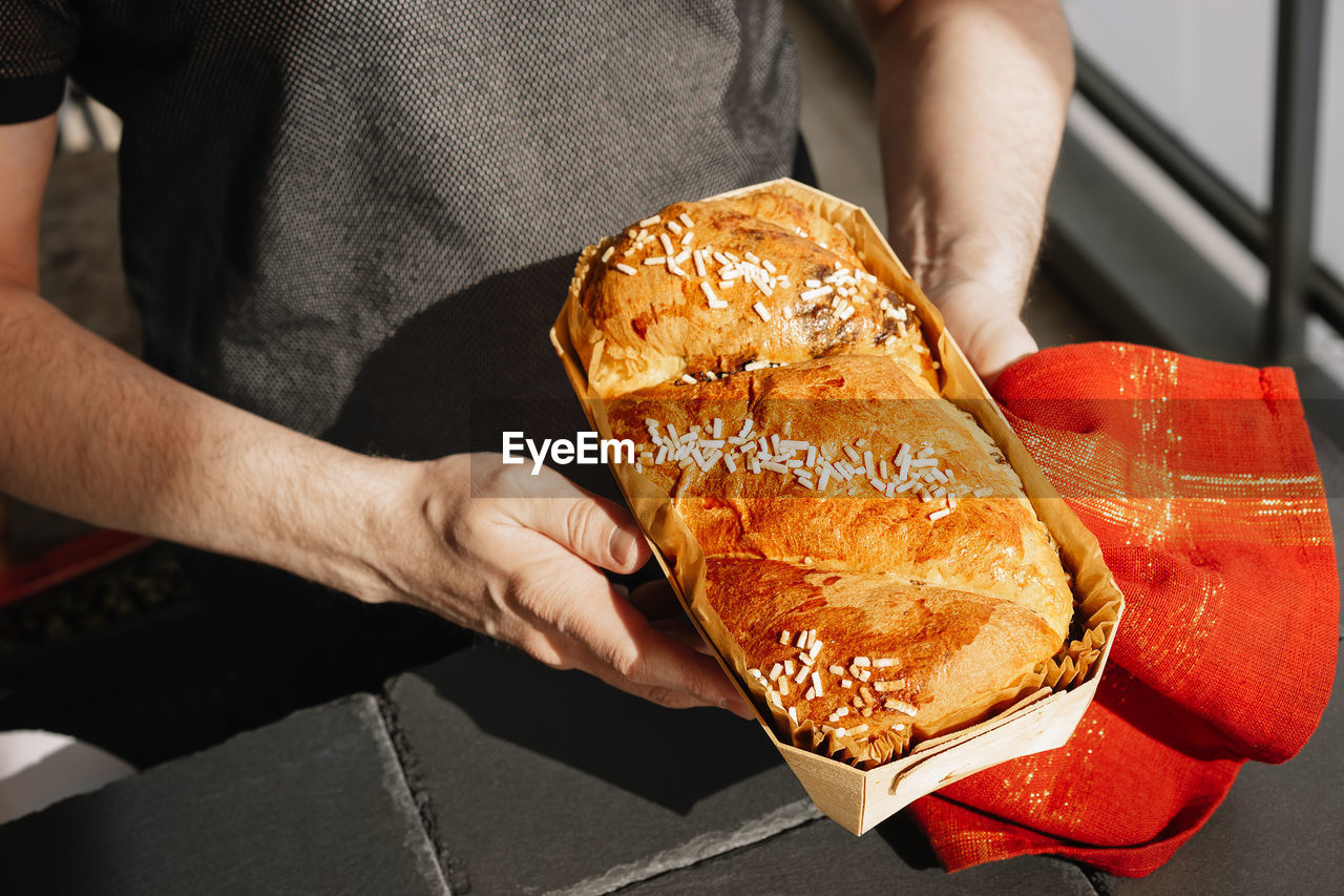 Midsection of man holding baked bread