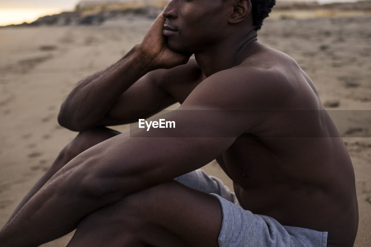 Midsection of man sitting at beach during sunset