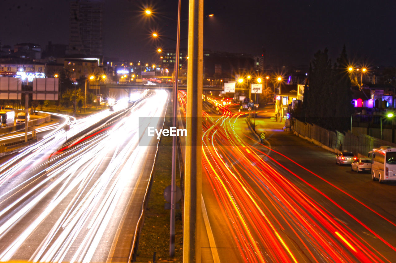 illuminated, long exposure, night, motion, light trail, city, street, transportation, blurred motion, speed, road, architecture, street light, city life, building exterior, high angle view, built structure, traffic, no people, city street, outdoors, cityscape, multiple lane highway, light, vehicle light