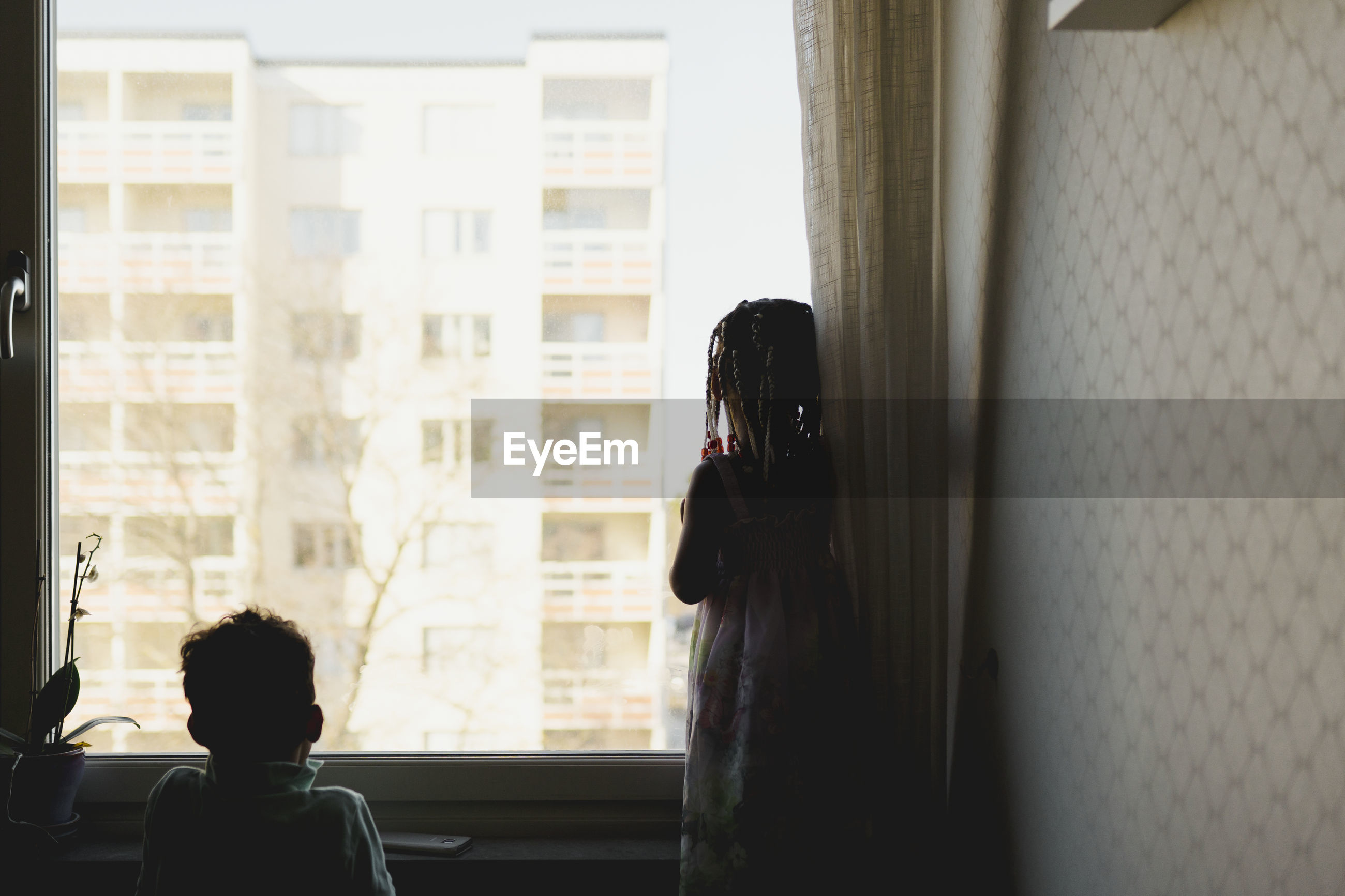 REAR VIEW OF PEOPLE LOOKING THROUGH WINDOW AT HOME