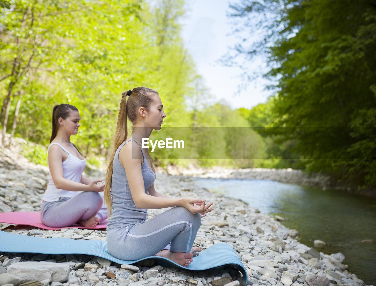 Women exercising near lake in forest
