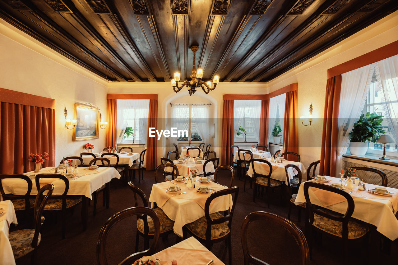 seat, indoors, chair, table, furniture, window, architecture, no people, absence, ceiling, wealth, restaurant, lighting equipment, business, luxury, empty, wood - material, food and drink, chandelier, illuminated, glass, setting, ornate, electric lamp