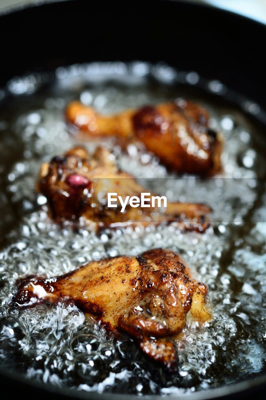 Close-up of chicken wings frying in cast iron skillet