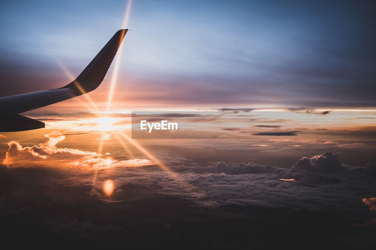 Cropped Image Of Airplane Flying Against Sky During Sunset
