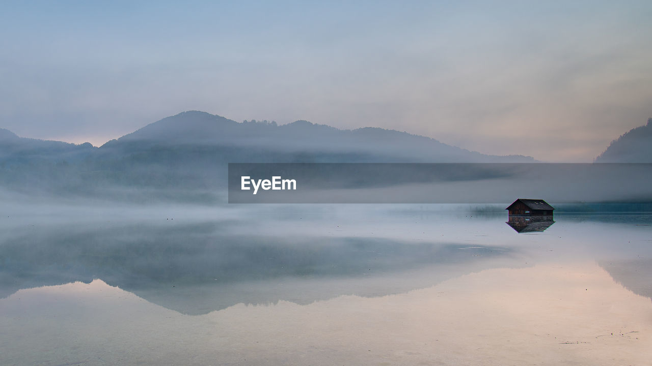 scenics - nature, beauty in nature, water, tranquility, mountain, tranquil scene, sky, non-urban scene, nature, idyllic, waterfront, cloud - sky, reflection, sea, no people, day, fog, mountain range, outdoors