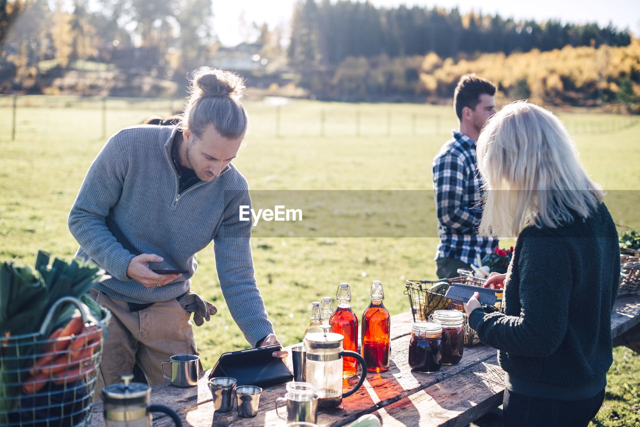 real people, food and drink, standing, casual clothing, women, day, adult, nature, togetherness, young men, young adult, leisure activity, lifestyles, food, three quarter length, men, land, preparation, table, friendship, outdoors, preparing food