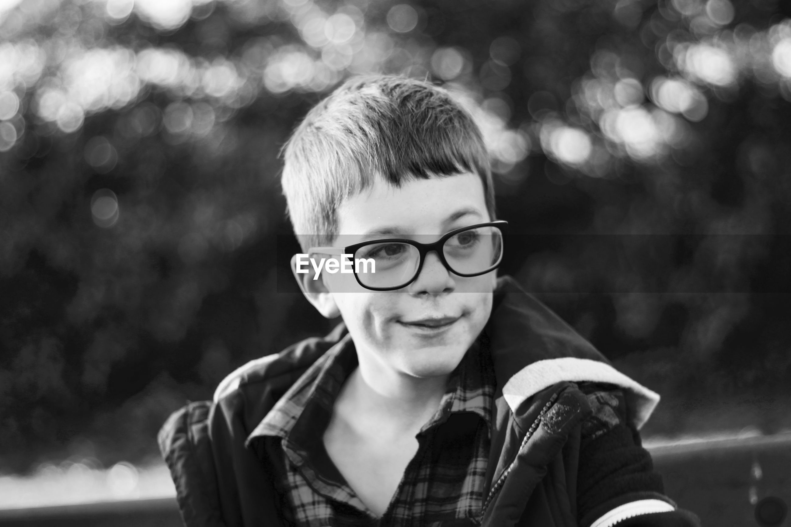 Close-up of cute boy wearing eyeglasses looking away while standing outdoors