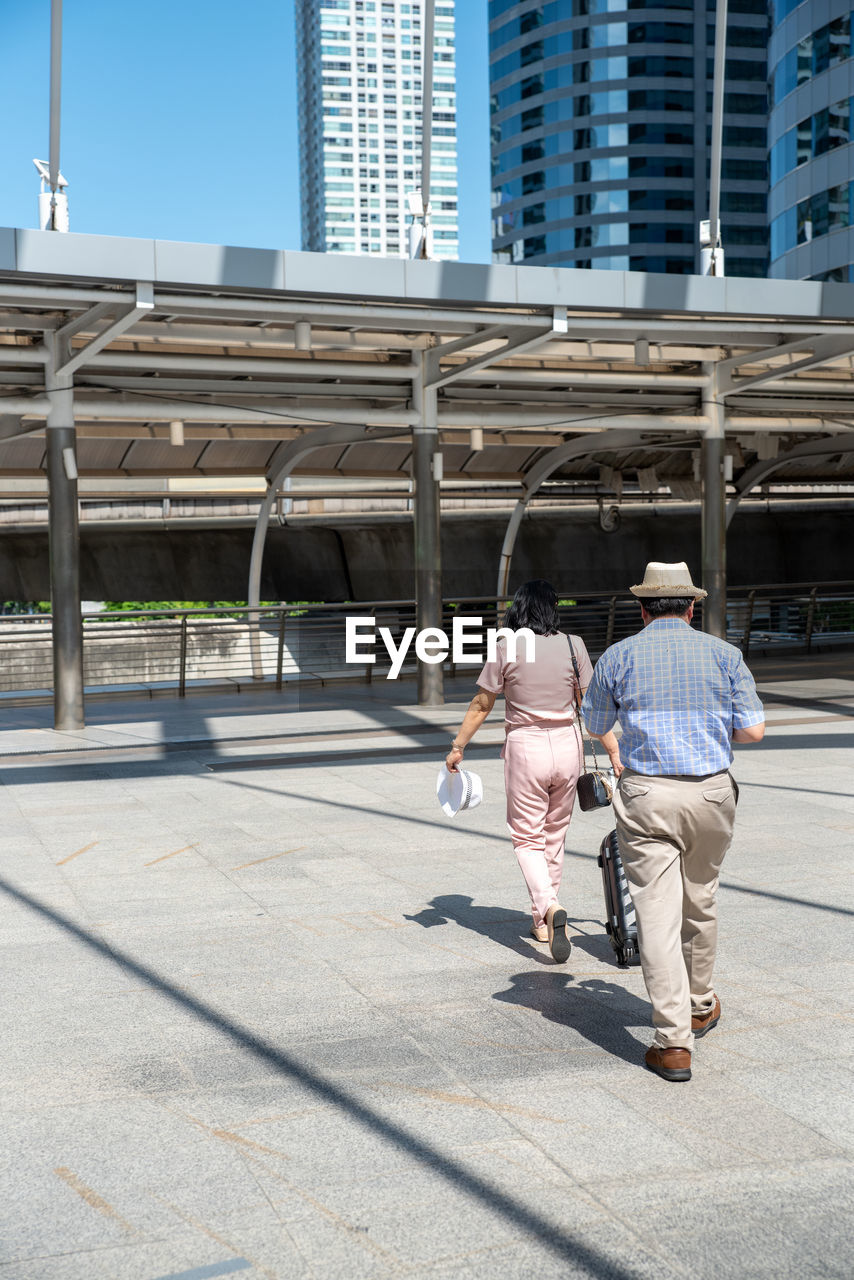 Rear view of couple walking on footpath in city