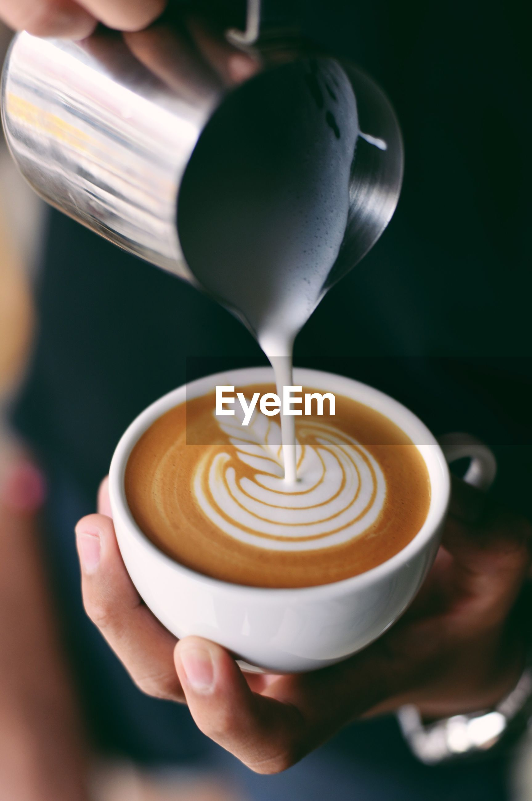 Close-up of cappuccino holding coffee cup