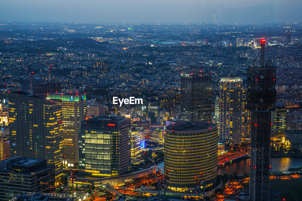 HIGH ANGLE VIEW OF ILLUMINATED MODERN BUILDINGS IN CITY