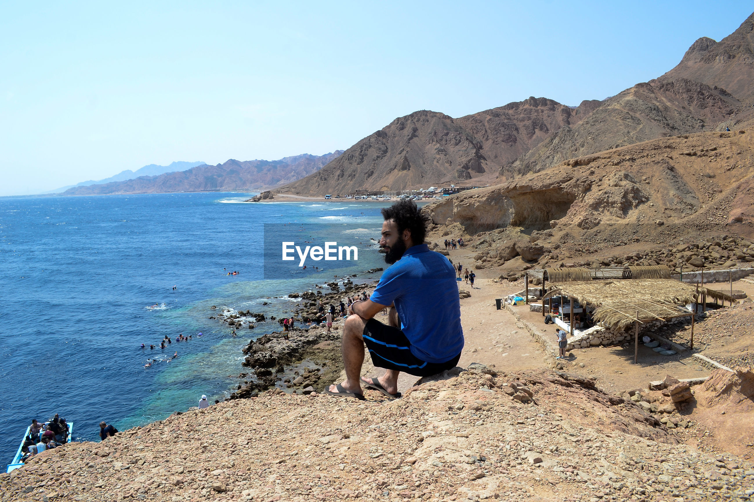 Side view of man looking at sea while sitting on mountain
