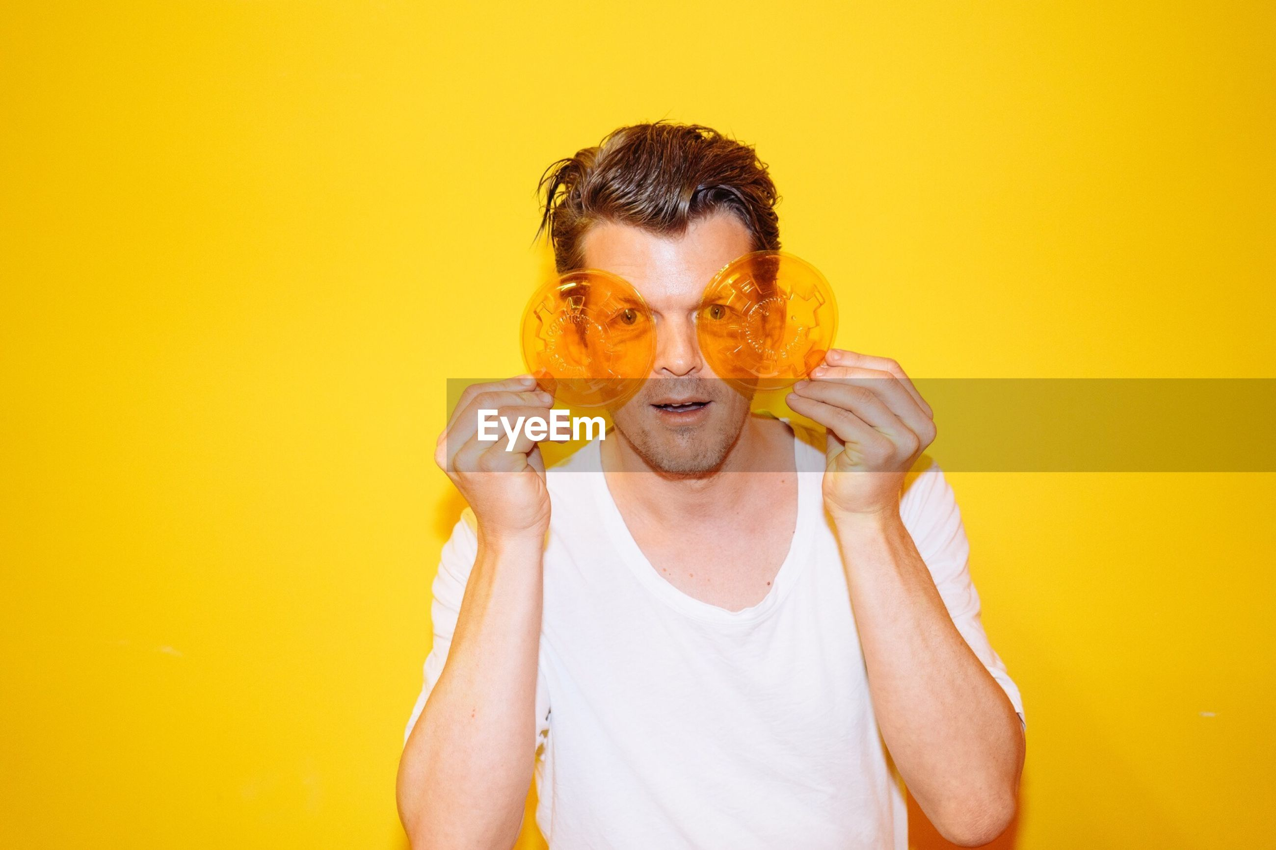 Young man holding see through lids over eyes against yellow background
