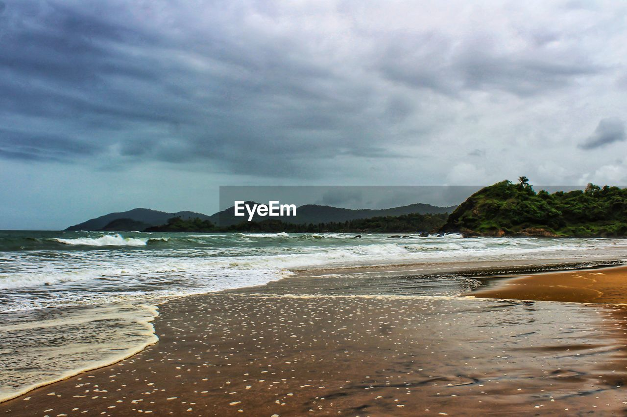 beach, cloud - sky, water, land, sky, sea, beauty in nature, scenics - nature, sand, mountain, nature, tranquility, tranquil scene, day, no people, wave, motion, aquatic sport, outdoors