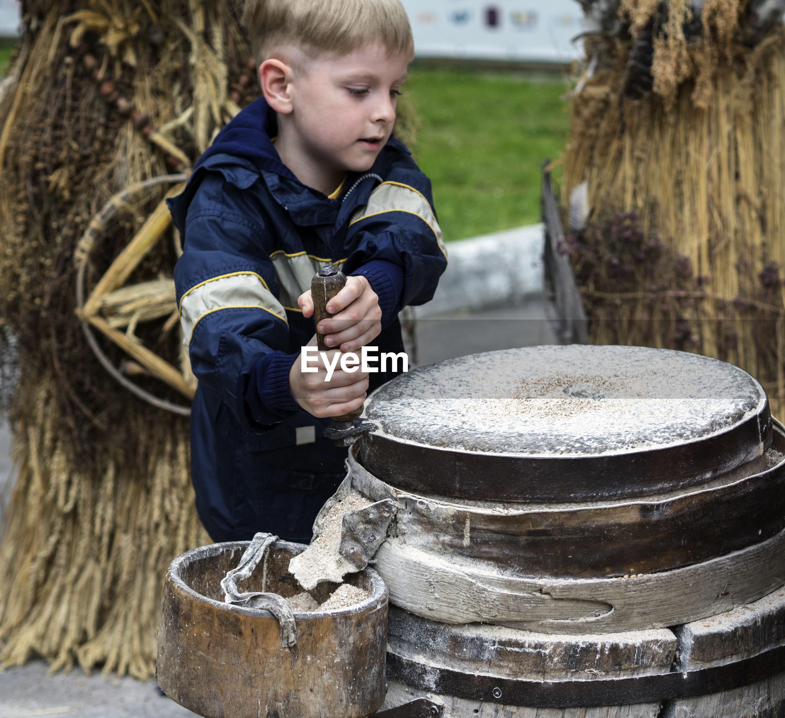 Boy grinding flour on millstones