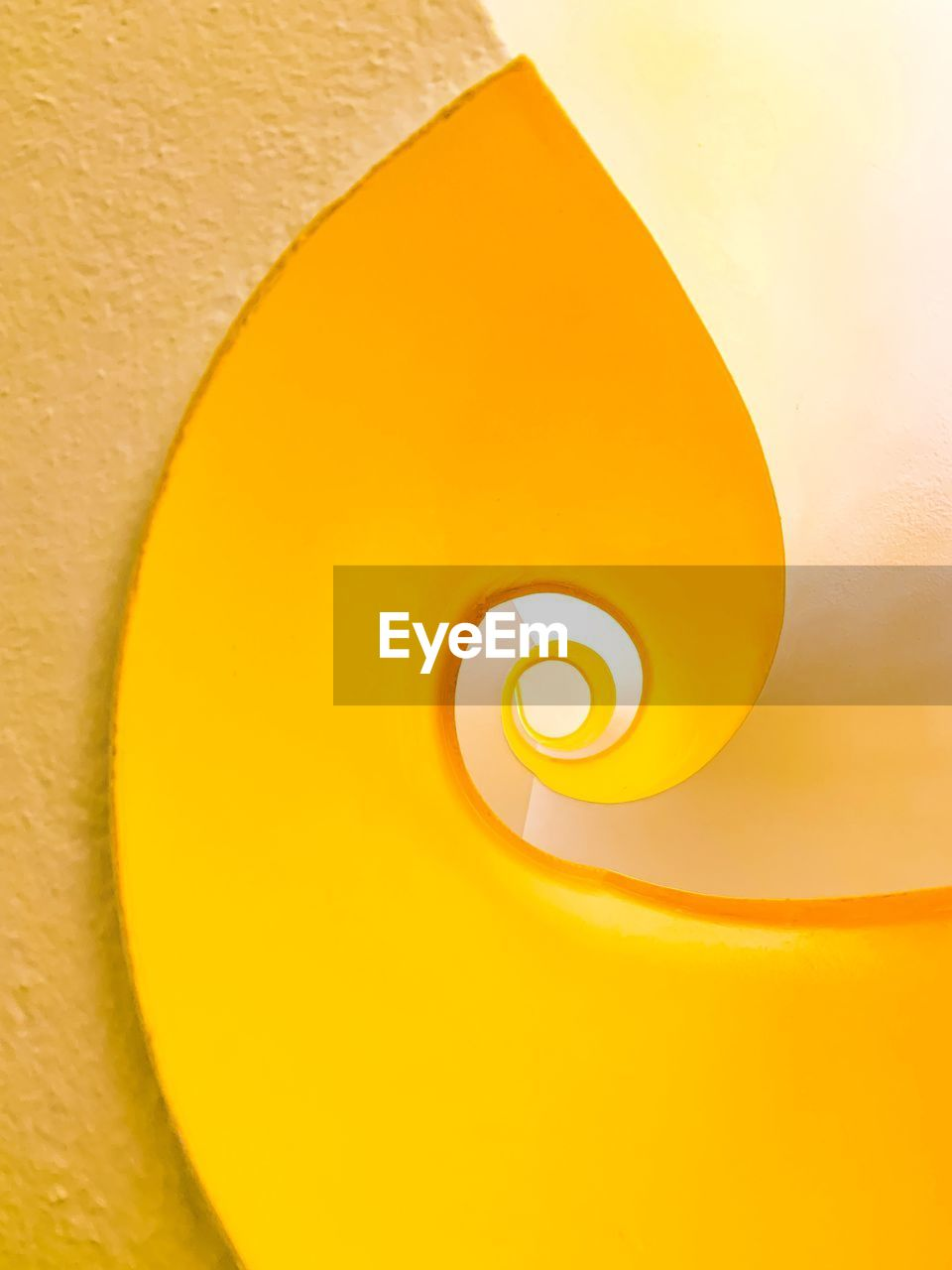 yellow, indoors, close-up, no people, illuminated, lighting equipment, spiral, white color, electric lamp, light, still life, geometric shape, orange color, nature, pattern, yellow background, studio shot, shape, high angle view