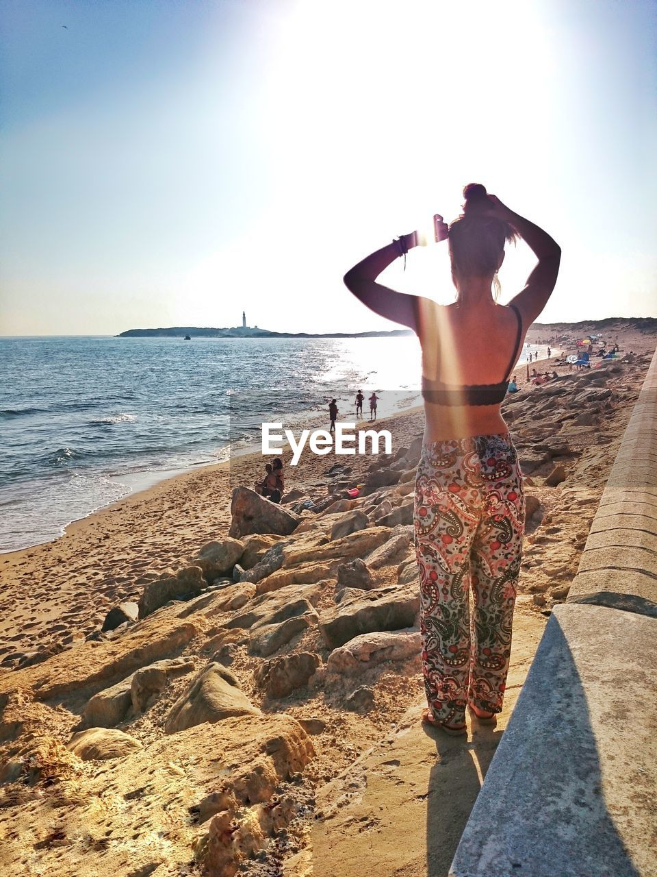 sea, real people, beach, rear view, lifestyles, standing, leisure activity, one person, water, full length, horizon over water, sky, sand, scenics, day, sunlight, beauty in nature, nature, outdoors, men, vacations, women, clear sky, young adult, young women, people