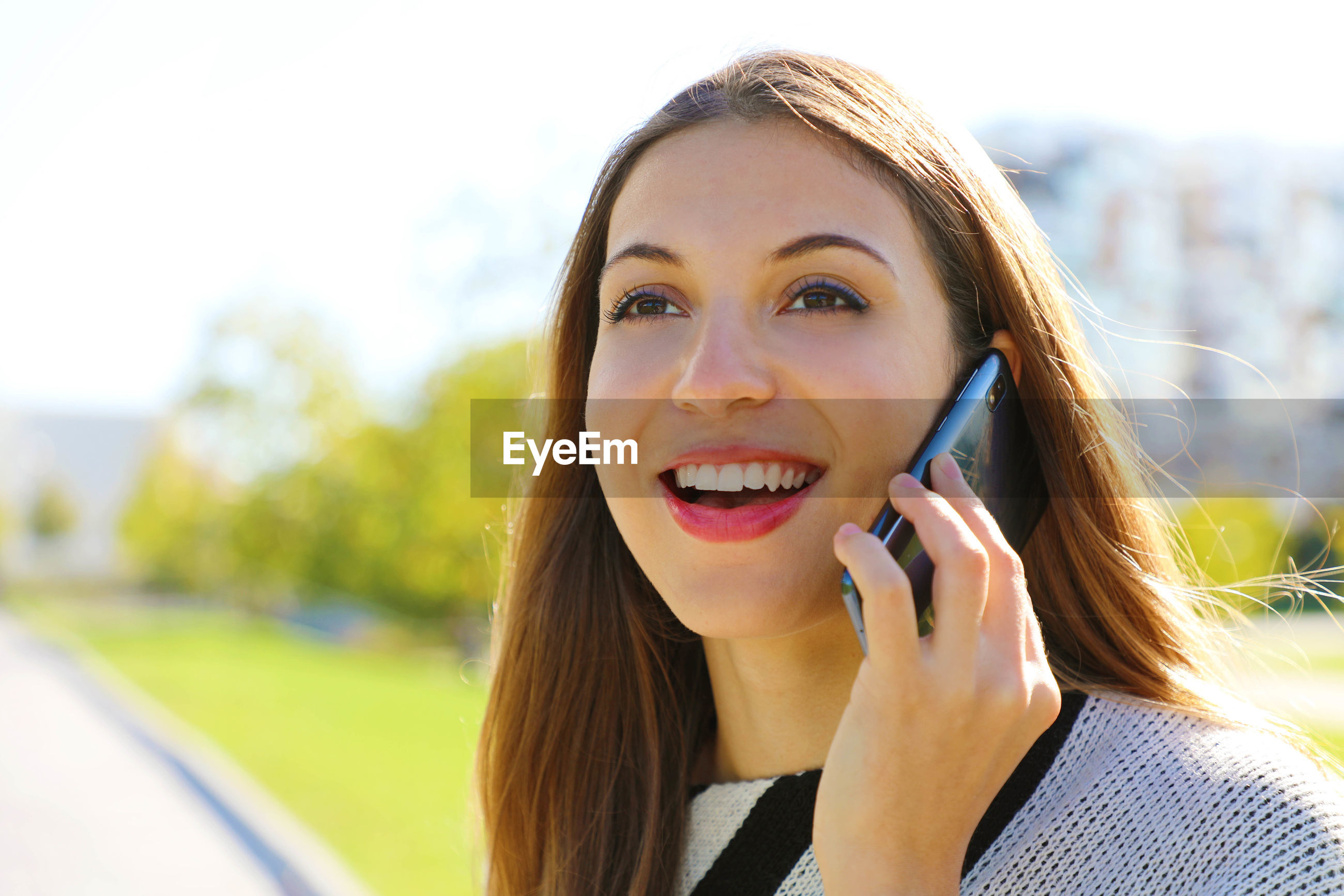 Close-up of smiling young woman using mobile phone while standing outdoors