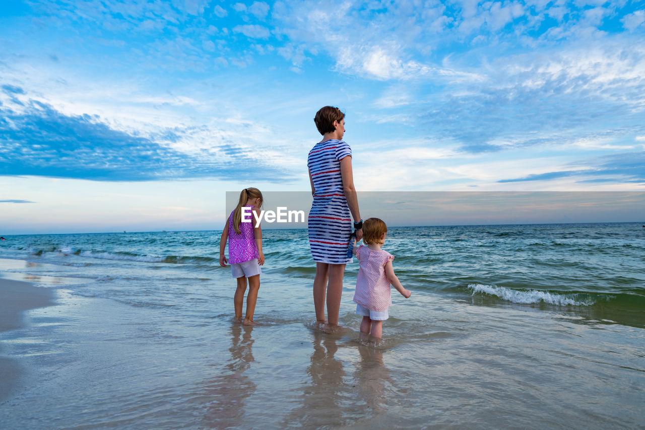 Rear View Of Siblings Standing On Beach Against Sky