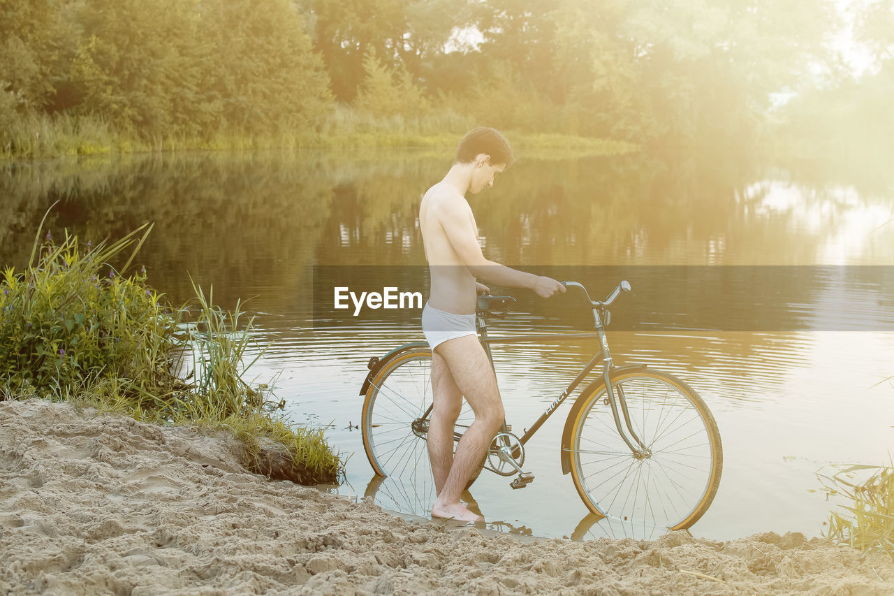 Side View Of Man Wearing Underwear Standing With Bicycle At Riverbank