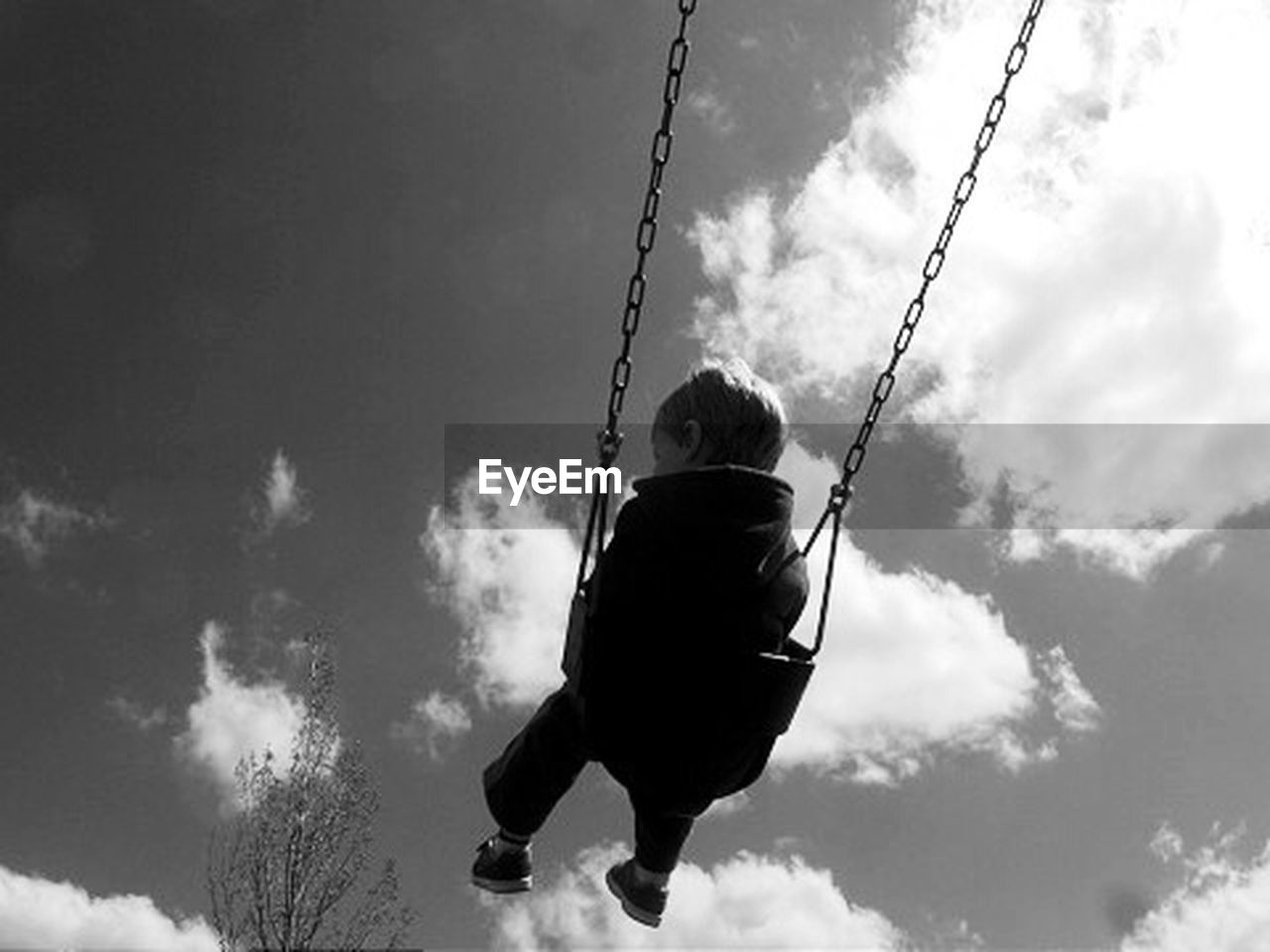 Low angle view of boy enjoying in swing against cloudy sky