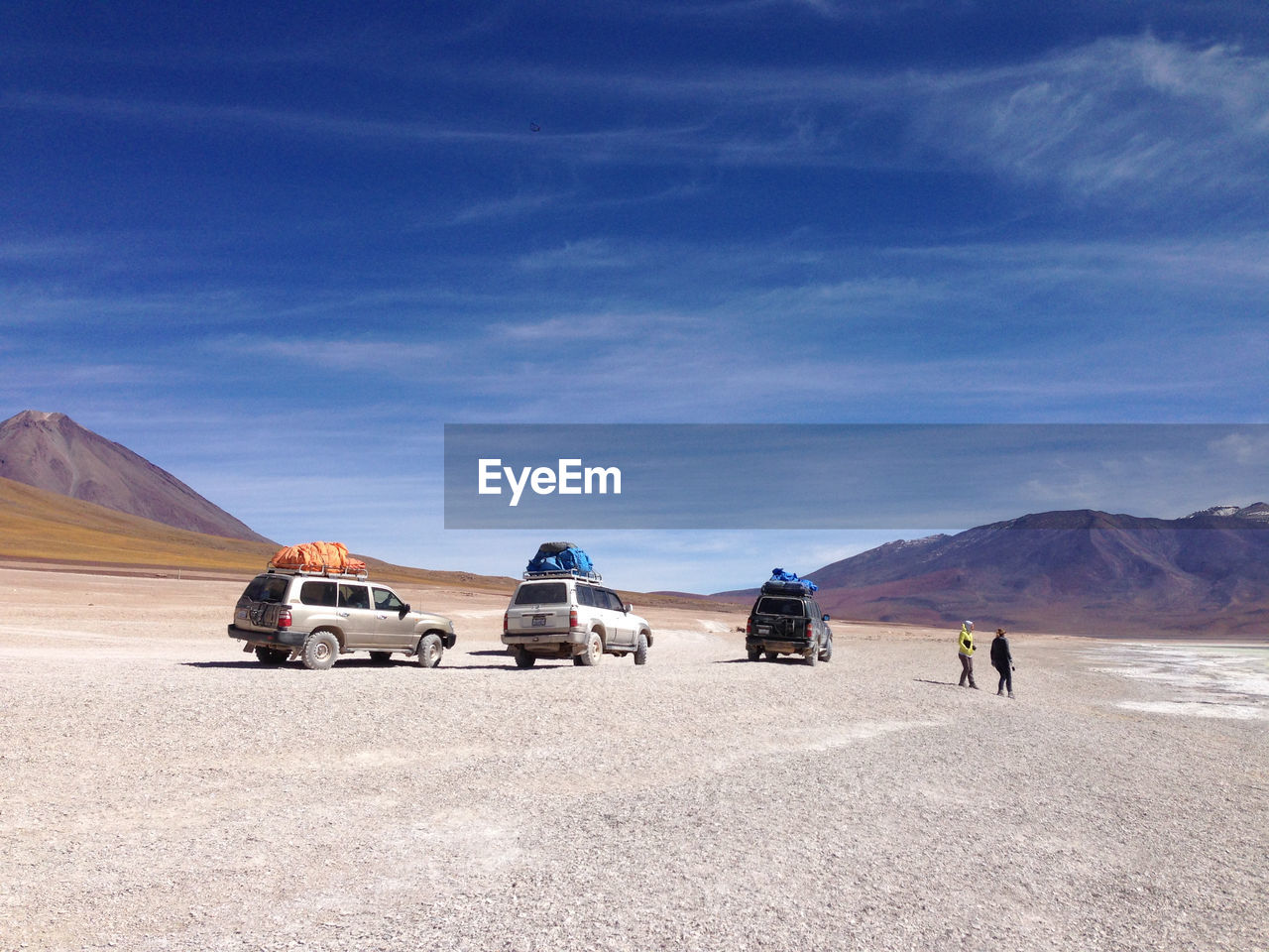 People By Vehicles On Desert Against Sky