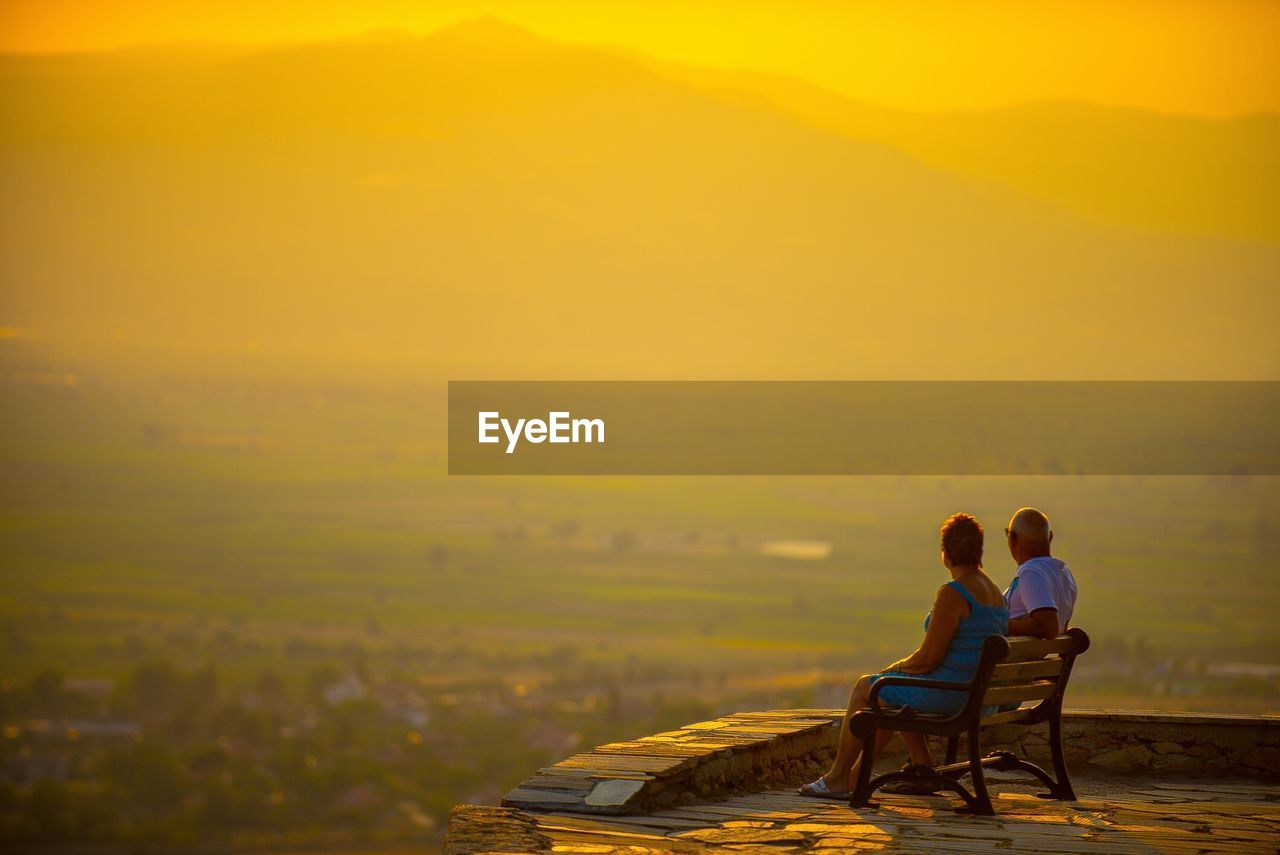 View of couple sitting on landscape against sky during sunset