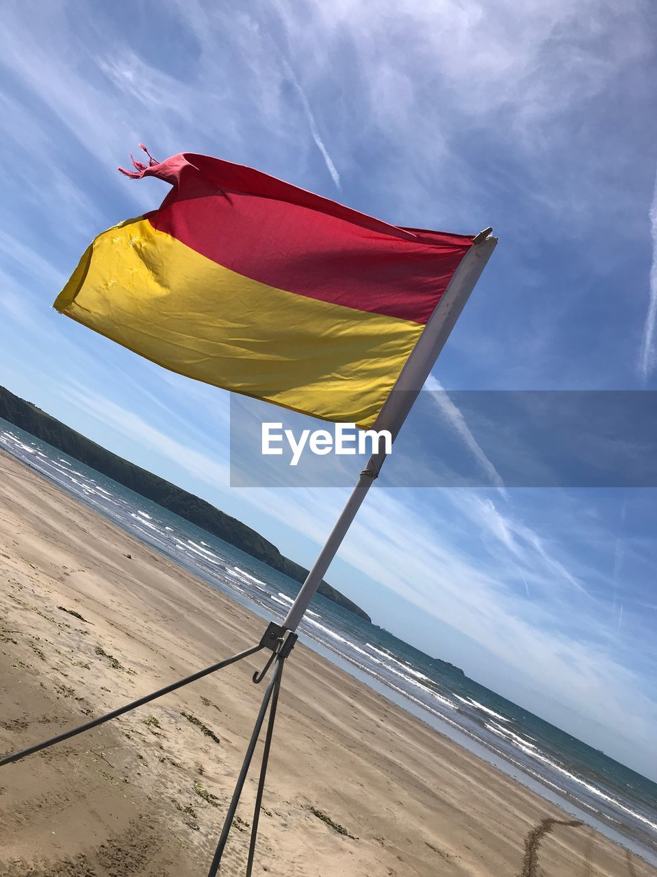 Close-up of flag waving at beach against sky