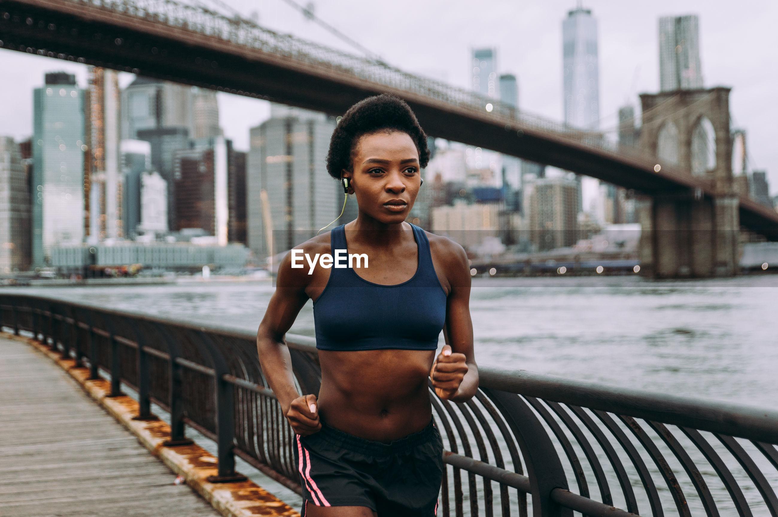 Woman running on promenade against bridge in city