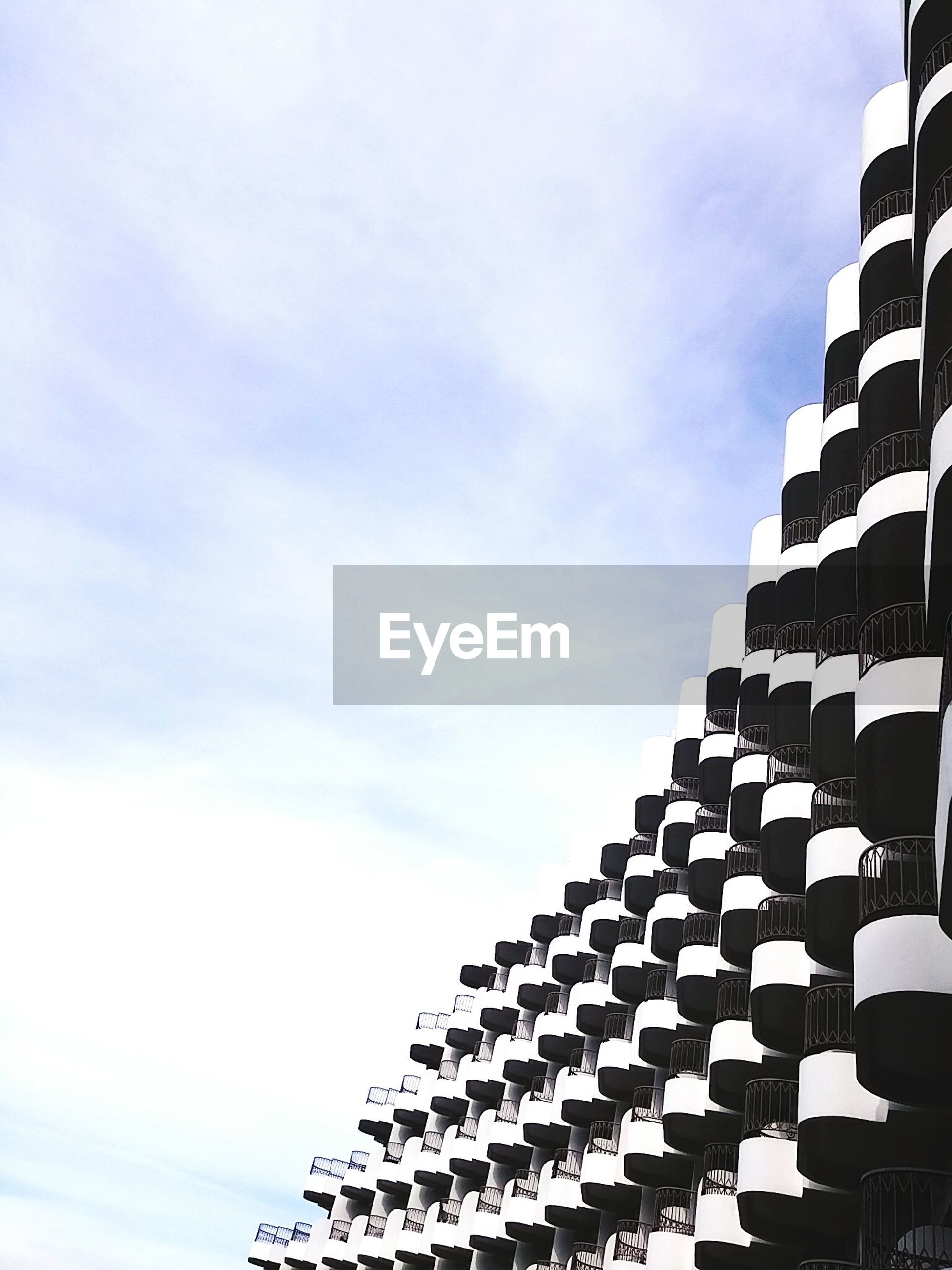 architecture, built structure, low angle view, building exterior, sky, pattern, cloud - sky, repetition, roof, in a row, design, day, cloud, modern, no people, architectural feature, outdoors, building, sunlight, city