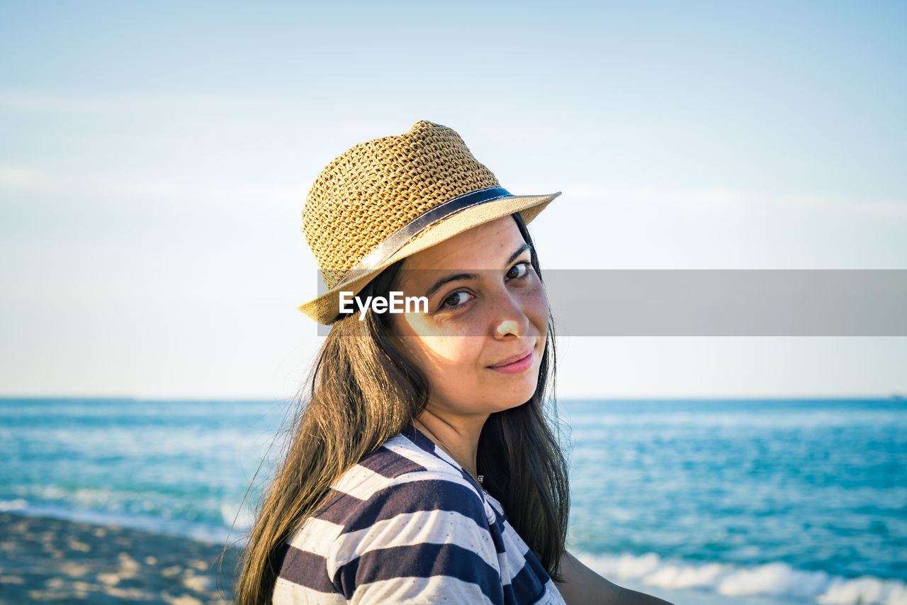 Side View Portrait Of Woman Wearing Hat At Beach
