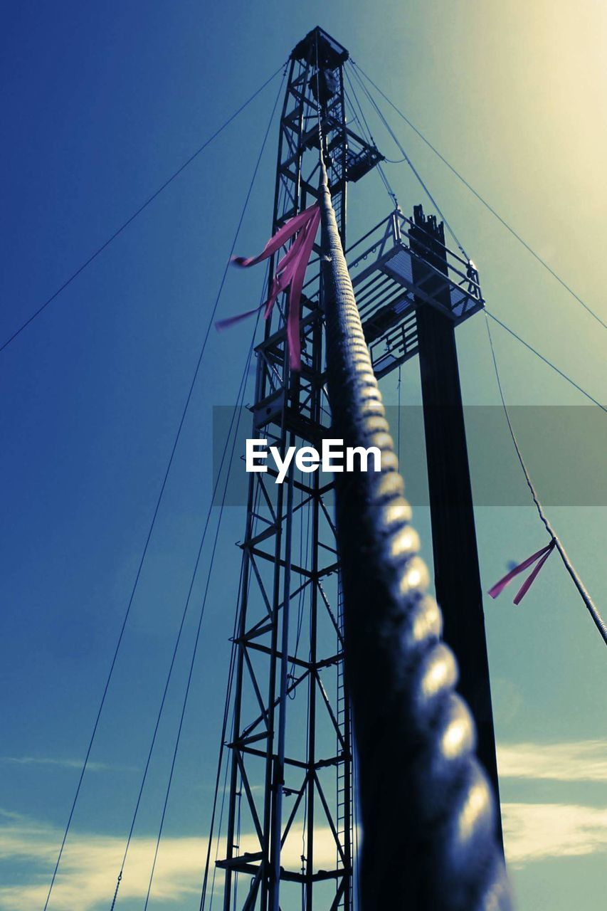 low angle view, sky, cable, architecture, built structure, no people, connection, electricity, nature, outdoors, tall - high, fuel and power generation, metal, blue, power line, technology, rope, arts culture and entertainment, electricity pylon, day, complexity, power supply, sailboat