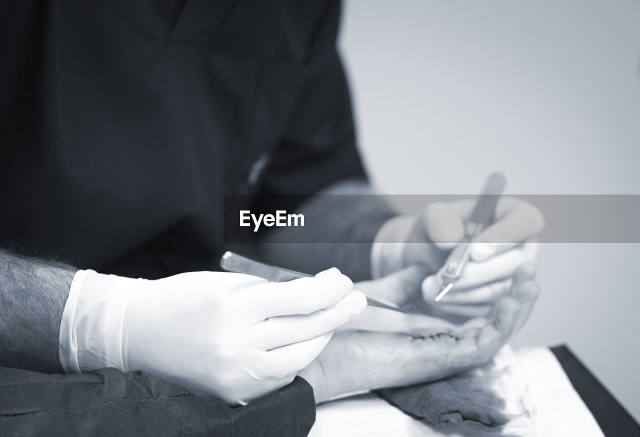 Midsection of doctor stitching hand of patient