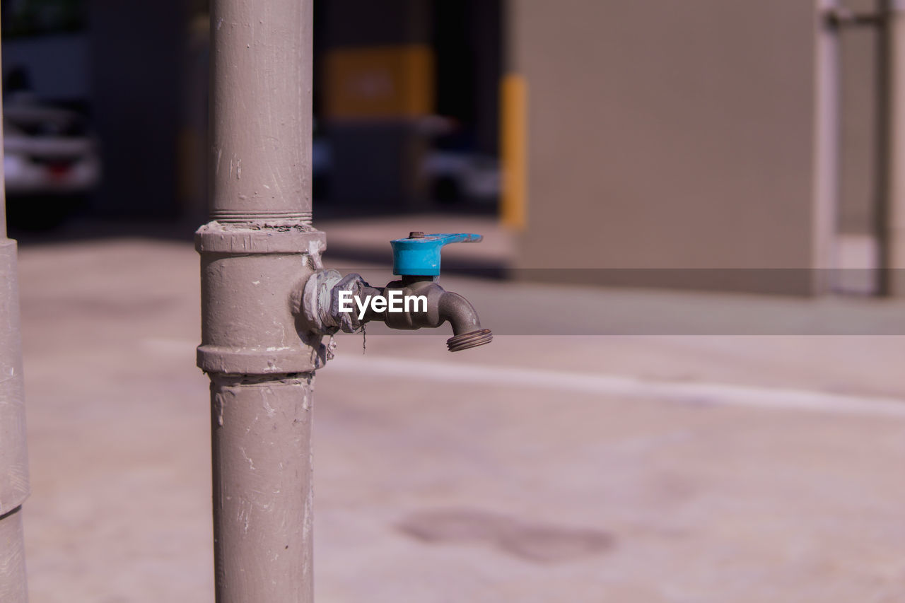 CLOSE-UP OF FAUCET AGAINST POLE