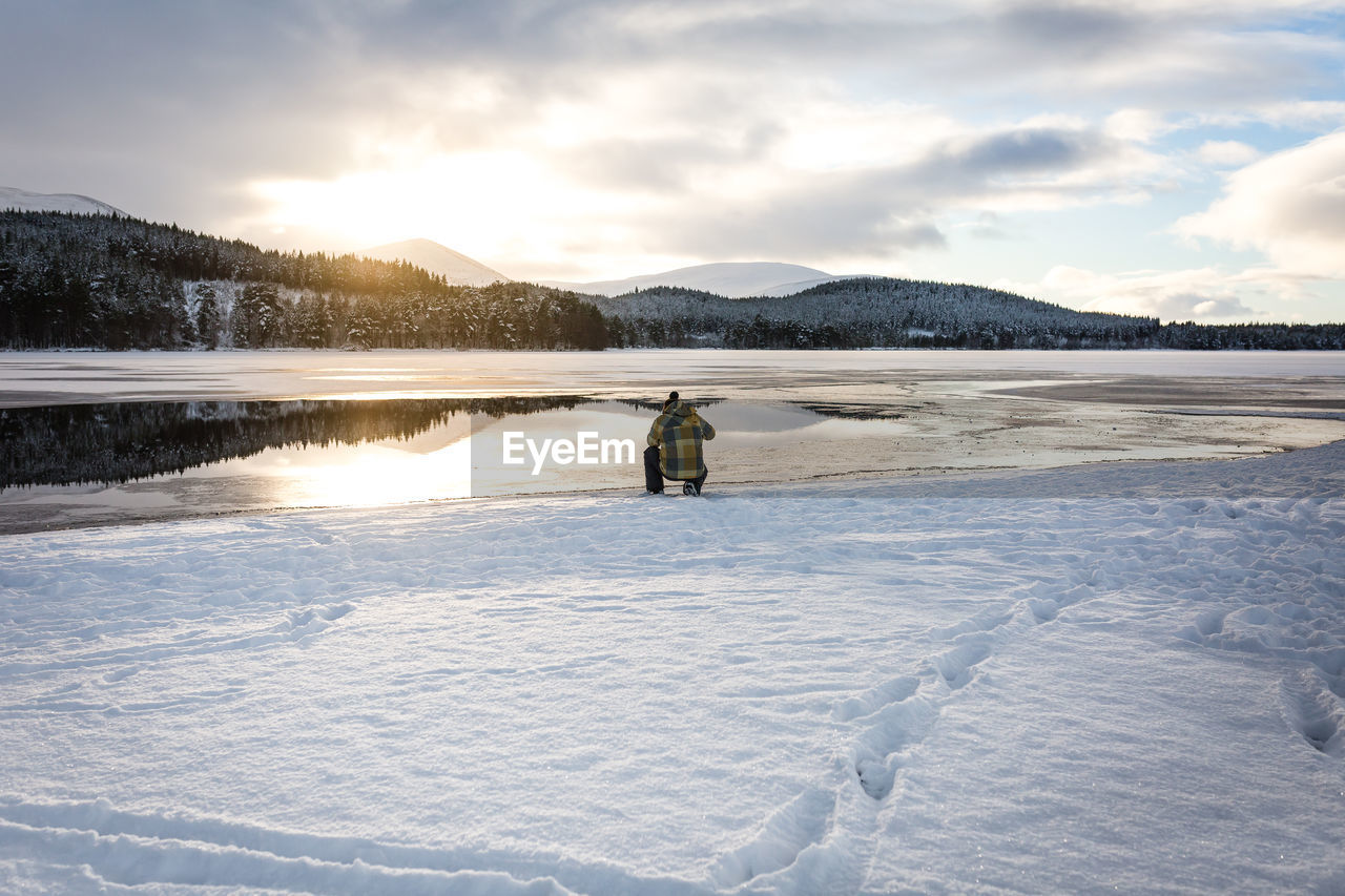 Rear view of man crouching on lakeshore against cloudy sky during winter