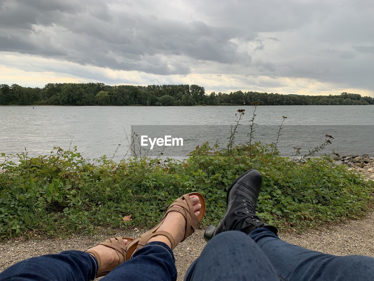 water, personal perspective, real people, human leg, low section, sky, lifestyles, one person, leisure activity, body part, cloud - sky, lake, human body part, plant, beauty in nature, nature, shoe, men, jeans, outdoors, human foot