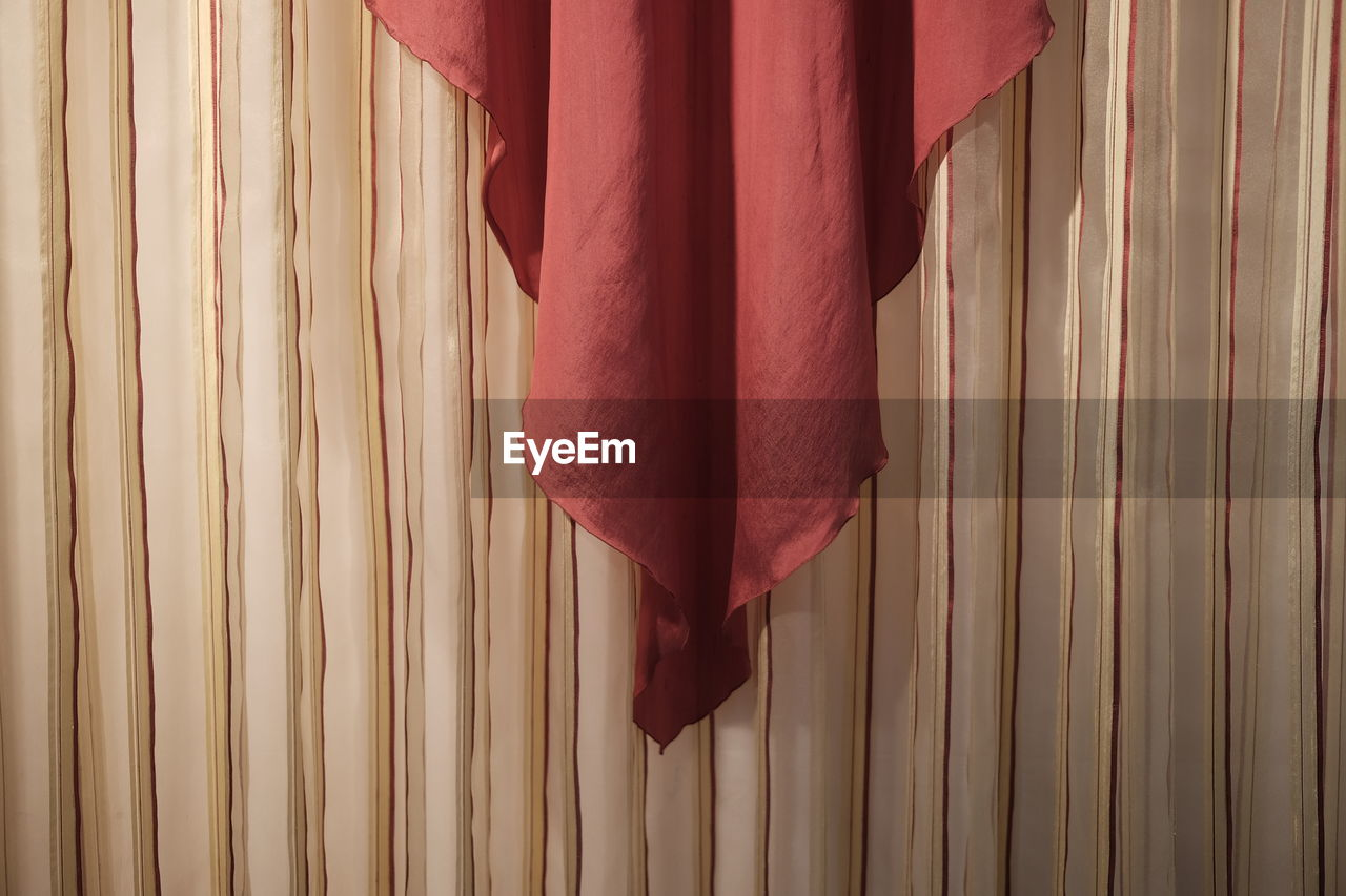 Close-up of red fabric hanging on wall