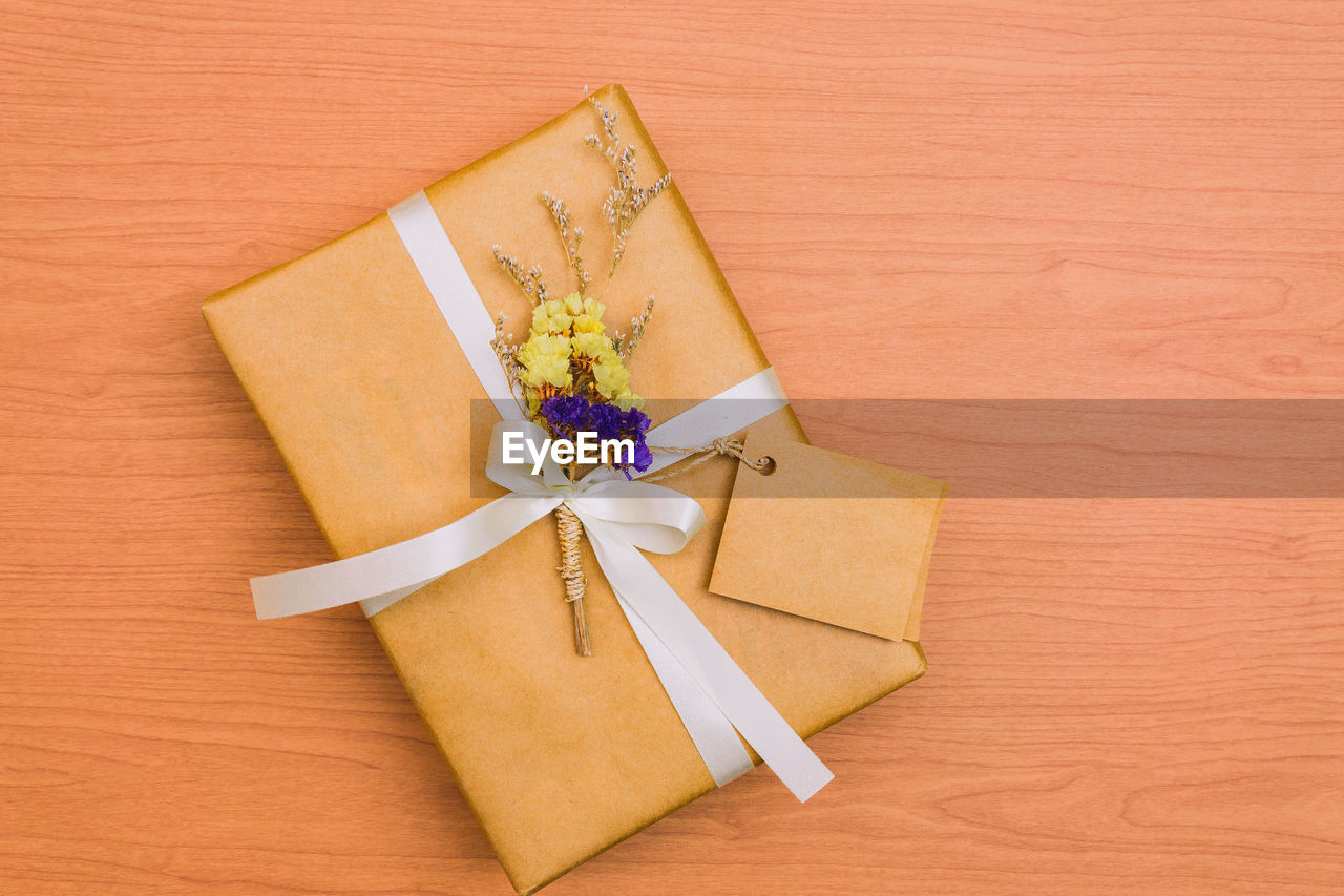 gift, ribbon, bow, tied bow, paper, ribbon - sewing item, box, gift box, table, still life, high angle view, box - container, indoors, surprise, no people, wrapped, wrapping paper, wood - material, close-up, celebration, package