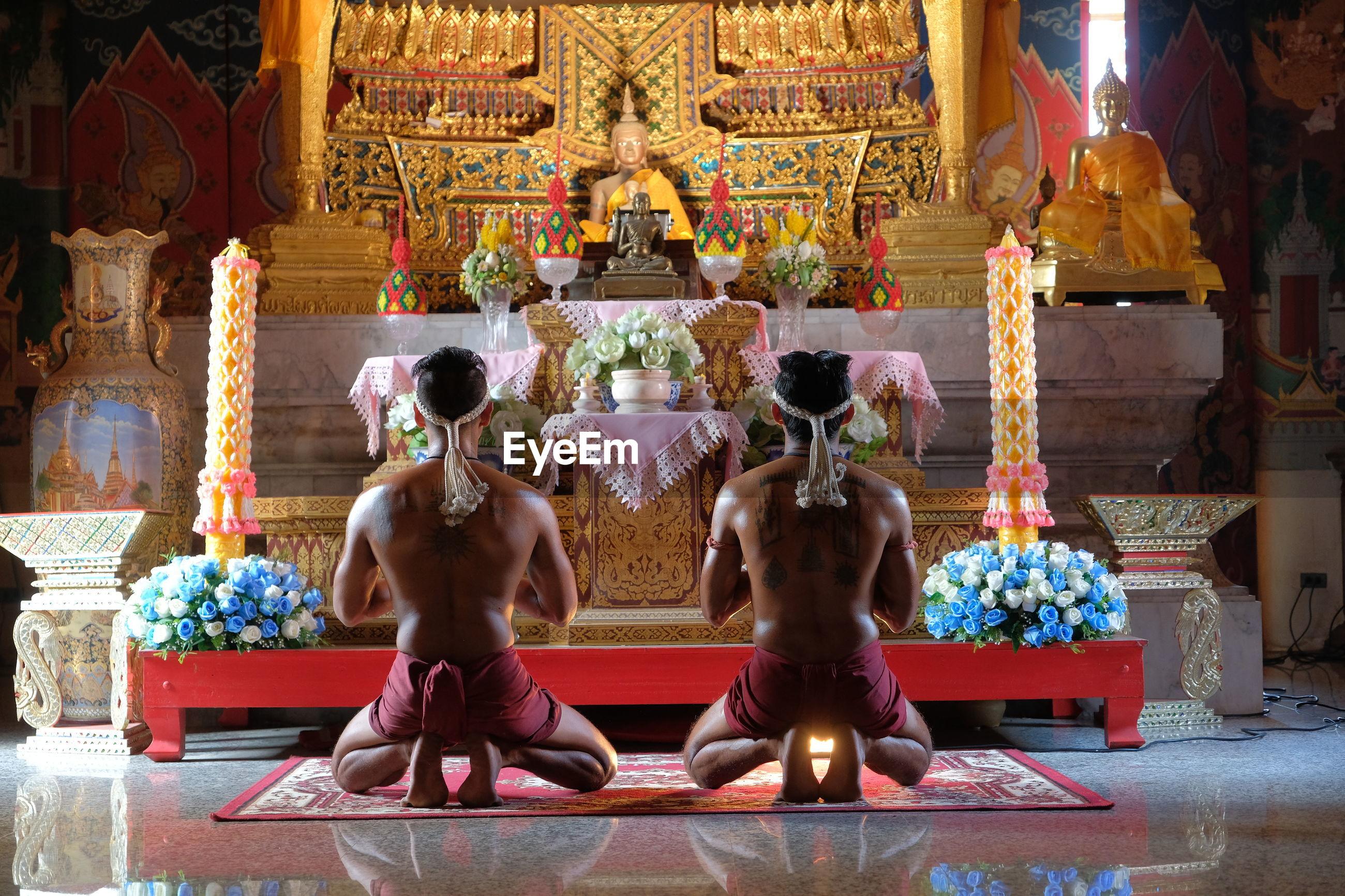 Rear view of shirtless men praying in buddhist temple