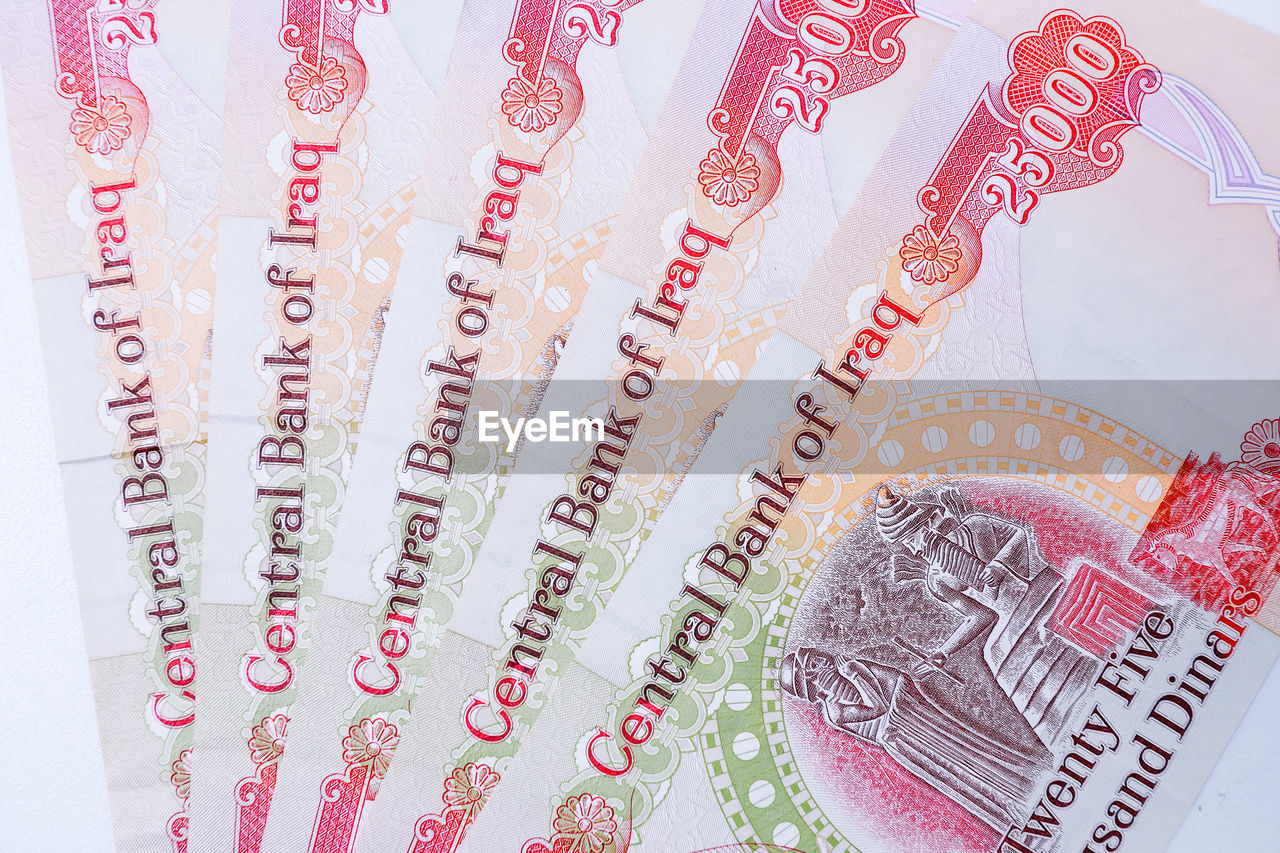 close-up, no people, western script, text, communication, currency, pattern, number, high angle view, celebration, still life, indoors, wealth, art and craft, finance, paper currency, jewelry, red, backgrounds, white color