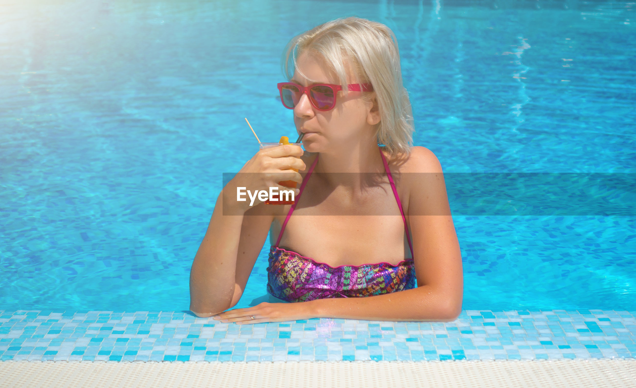 Woman looking away while drinking cocktail in swimming pool