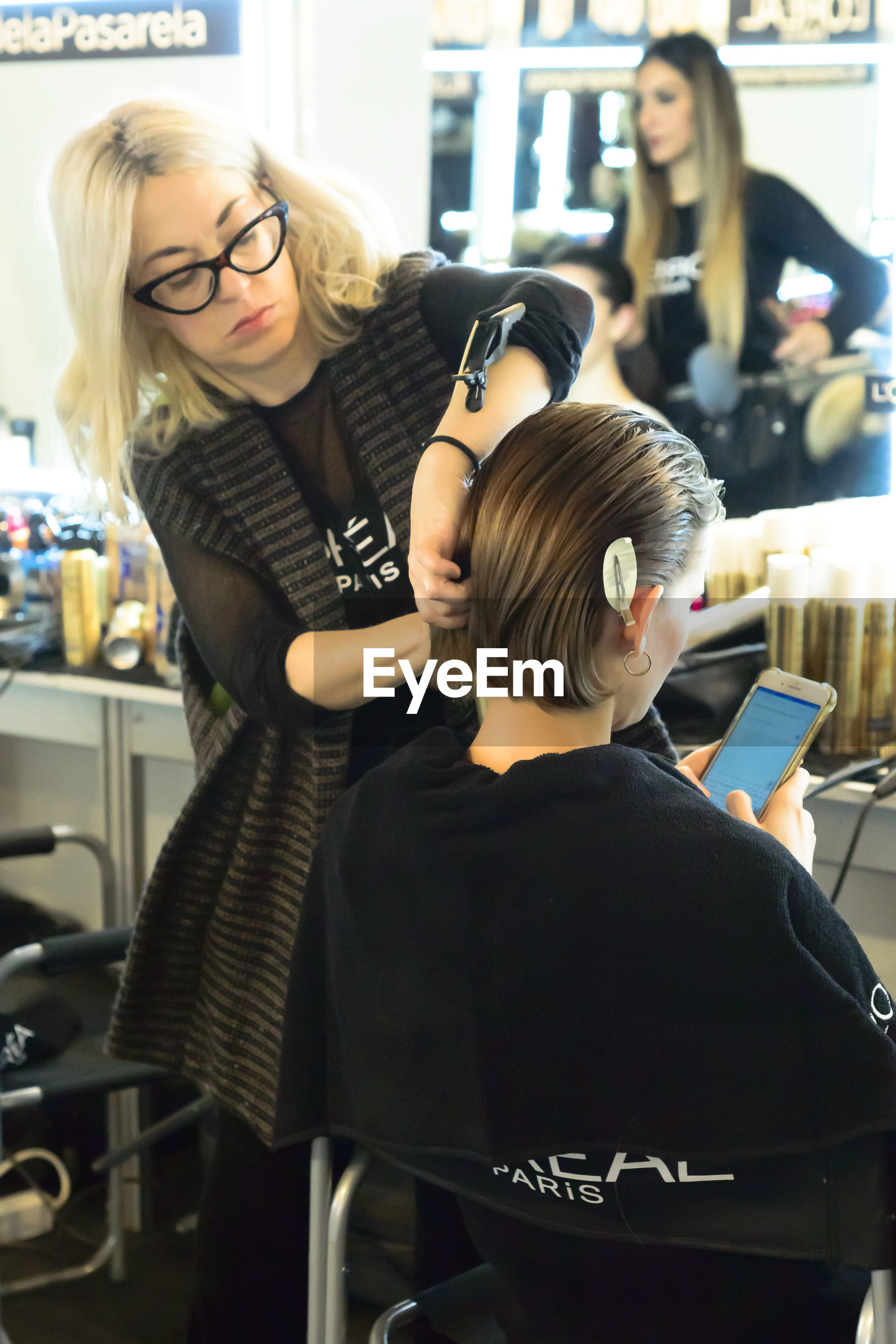 hairdresser, adult, women, indoors, eyeglasses, business, customer, occupation, female, hair salon, working, two people, small business, glasses, young adult, blond hair, business finance and industry, hairstyle, sitting, person, communication, standing, technology, men, clothing, entrepreneur, cutting hair, barber shop, office, lifestyles, expertise, service, casual clothing, computer, fashion