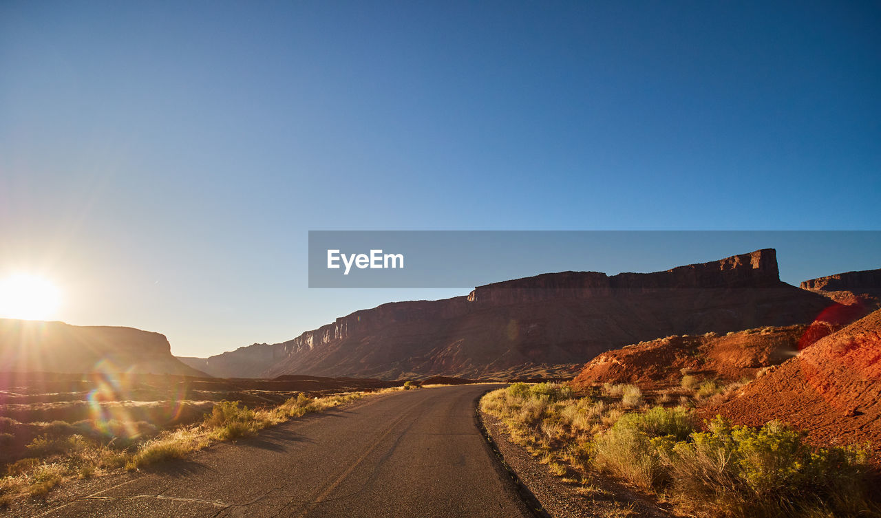 sky, road, sunlight, the way forward, nature, direction, beauty in nature, clear sky, mountain, tranquility, landscape, tranquil scene, copy space, transportation, scenics - nature, non-urban scene, environment, no people, sunbeam, day, sun, lens flare, mountain range, outdoors, diminishing perspective, bright, formation