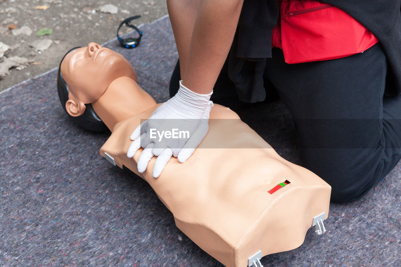 Low section of person performing cpr on dummy