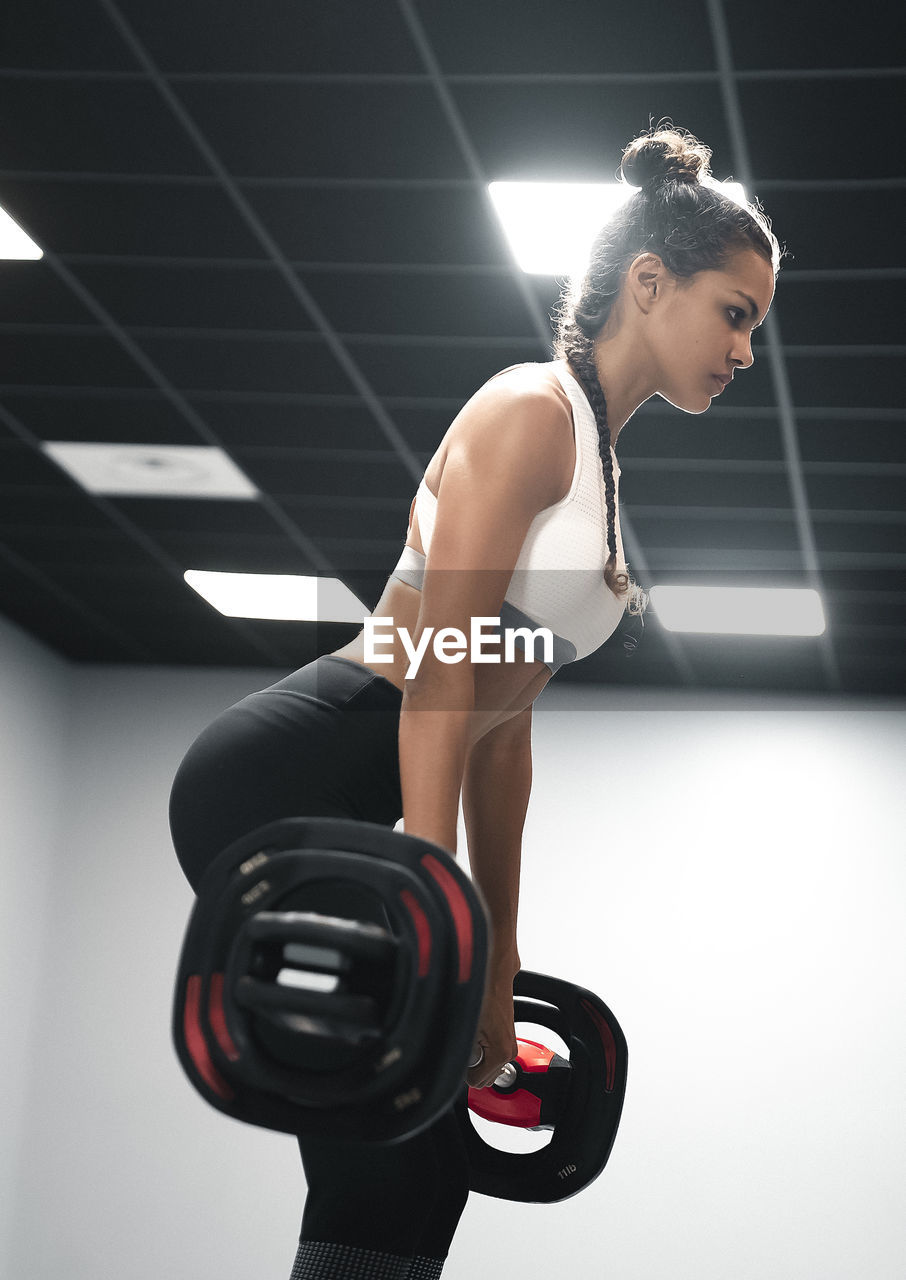 exercising, sport, healthy lifestyle, lifestyles, indoors, sports clothing, sports training, clothing, strength, young adult, one person, women, full length, gym, vitality, young women, exercise equipment, side view, hairstyle, physical activity, weight training, body conscious, effort, beautiful woman